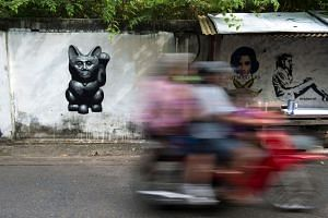 A graffiti caricature of Thailand's junta chief depicted as a Lucky Cat with a paw raised to rake in money in Bangkok, on Sept 4, 2018.