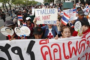 Thai pro-democracy protesters shout slogans as they march toward Government House during a rally in Bangkok on May 22, 2018.