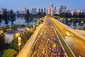 Participants of the 18.45km race making their way along Nicoll Highway before the break of dawn yesterday.