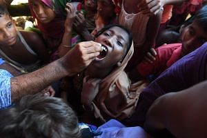 A Rohingya refugee receives an oral cholera vaccine from a Bangladeshi volunteer at the Thankhali refugee camp in Ukhia district, on Oct 10, 2017.