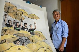Local artist Fong So poses next to an artwork he produced during the pro-democracy rallies at his studio in Hong Kong.