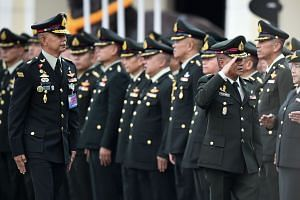 General Apirat Kongsompong (left) follows outgoing Royal Thai Army chief General Chalermchai Sitthisad as he salutes during the handover ceremony in Bangkok on Sept 28, 2018.