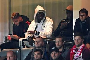 Pogba (in white) sitting in the stands during United's League Cup match against Derby County.