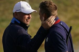 Europe's Danish captain Thomas Bjorn (left) congratulates Europe's Swedish golfer Henrick Stenson after he won his foursomes match.