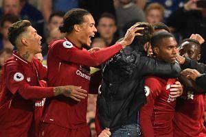 Liverpool's English striker Daniel Sturridge (right) celebrates with team mates after scoring.