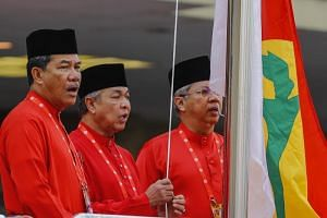 United Malays National Organisation (UMNO) party president Zahid Hamidi (Centre) with his deputy Mohamad Hasan (Left) and secretary-general Annuar Musa (Right) sing as they raise the party flag during the opening ceremony of UMNO General Assembly in