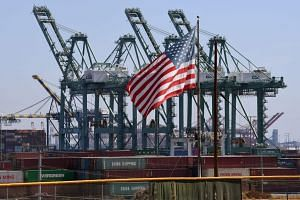 The US flag flies over Chinese shipping containers that were unloaded at the Port of Long Beach, in Los Angeles County, on Sept 29, 2018.
