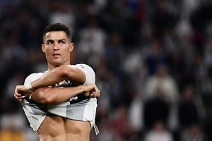 Juventus' Portuguese forward Cristiano Ronaldo takes off his jersey at the end of the Italian Serie A football match between Juventus and Napoli on Sept 29, 2018 at the Juventus stadium in Turin.