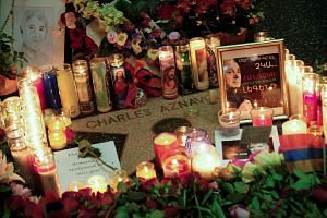 Flowers and candles are placed on Aznavour's Star on The Hollywood Walk of Fame.