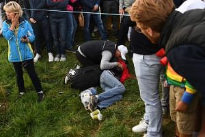 People gather around an injured spectator during a fourball match on the first day of the 42nd Ryder Cup.
