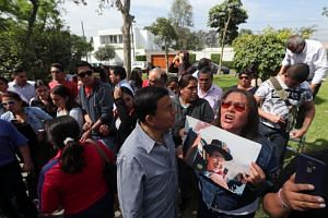 A supporter holds a picture of Alberto Fujimori as people wait outside Fujimori's residence in Lima.