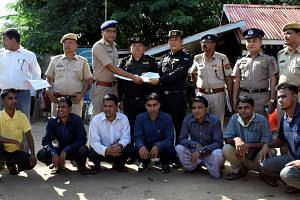 The seven Rohingya men to be deported sit as Indian and Myanmar security officials exchange documents before their deportation on India-Myanmar border at Moreh in the northeastern state of Manipur, India, Oct 4, 2018.