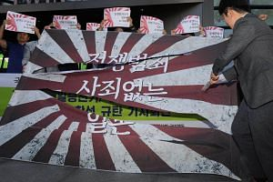 """South Korean protesters tear a """"Rising Sun""""  Flag during a rally against the Japanese government near the Japanese Embassy in Seoul, South Korea, on Oct 1, 2018."""