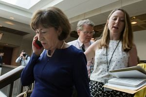 Republican Senator Susan Collins (left) walks to a room to read the report on the FBI probe into Kavanaugh.