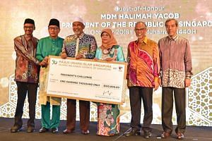 President Halimah Yacob receiving a cheque of $100,000 for the President's Challenge during the Muis Awards ceremony on Oct 6, 2018.