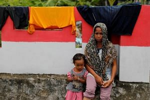 A mother sits with her daughter at the epicentre of a devastating earthquake at Lende Tovea village in Donggala, Sulawesi, Indonesia, on Oct 6, 2018.
