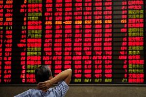 An investor looks at an electronic board showing stock information at a brokerage house in Shanghai on Sept 7, 2018.