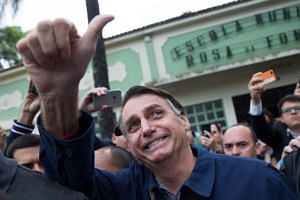 Brazil's right-wing presidential candidate Jair Bolsonaro gives a thumbs up after casting his vote at Villa Militar, during general elections, in Rio de Janeiro, on Oct 7, 2018.