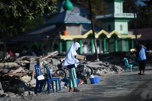 An child affected by the earthquake in Sulawesi asks for donations along a road in Donggala, on Oct 5, 2018.