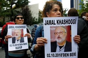 Human rights activists hold pictures of Saudi journalist Jamal Khashoggi during a protest outside the Saudi Consulate in Istanbul, Turkey, on Oct 9, 2018.