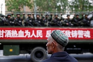 "An Uighur man looks on at an anti-terrorism oath-taking rally in Urumqi, Xinjiang. Rules were introduced to standardise controversial anti-terror ""re-education centres"" on Oct 9, 2018."