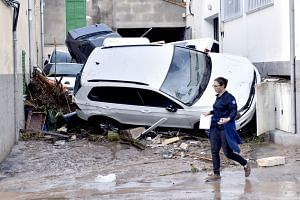 A resident walks past a pile of vehicles after they were damaged by flash floods in the village of Sant Llorenc des Cardasar.
