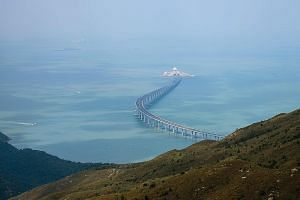 A section of the Hong Kong-Zhuhai-Macau Bridge (left) seen from Lantau island. Reclamation works for the development under Chief Executive Carrie Lam's (above)