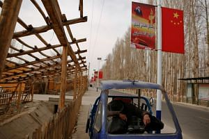 A man rests under a poster showing Chinese President Xi Jinping in the Xinjiang Uighur Autonomous Region. Beijing blames Uighur separatist groups for violent attacks in the region.