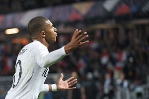 Mbappe celebrates after scoring from a penalty kick.