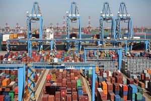 A cargo ship is seen behind containers at an automated container terminal in Qingdao port, Shandong province, China.