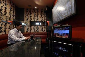Businessman Hideyuki Aoki working in a rented room at a karaoke outlet in Tokyo, Japan, on Aug 30, 2018.