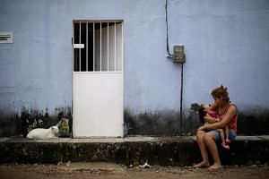 Ms Gabriela Alves de Azevedo, 22, holds her three-year-old daughter Ana Sophia, who was born with microcephaly, at their house in Olinda, Brazil, on Aug 7, 2018.