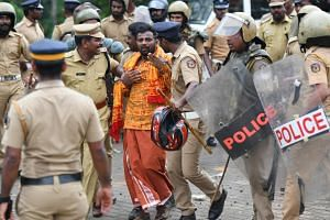 Indian police take a man into custody in Nilackal, in Kerala state, on Oct 17, 2018, as protesters rallied against a Supreme Court verdict revoking a ban on women's entry to the Lord Ayyappa temple.