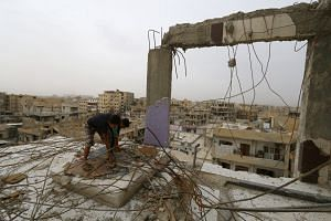 Boys are seen on a damaged building in Raqqa, Syria, on Oct 12, 2018.