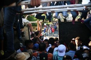 Honduran migrants taking part in a caravan heading to the US, aboard a truck in Metapa on their way to Tapachula, Chiapas state, Mexico, on Oct 22, 2018.