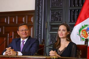 Peruvian Foreign Minister Nestor Popolizio (left) attends a news conference with Jolie.