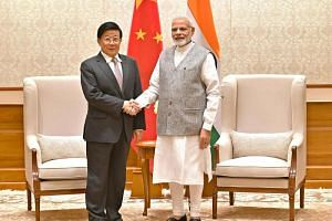 Chinese State Councilor and Minister of Public Security Zhao Kezhi (left) shakes hands with Indian Prime Minister Narendra Modi in New Delhi.