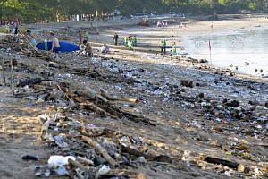 File photo of workers attempting a clean-up as trash washed up on Kuta beach by seasonal winds, on Feb 15, 2016.
