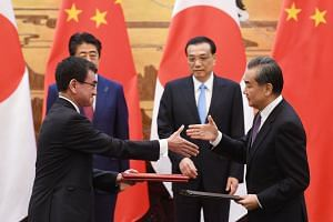 Japan's Foreign Minister Taro Kono (left) shakes hands with Chinese Foreign Minister Wang Yi (right) as Japan's Prime Minister Shinzo Abe and Chinese Premier Li Keqiang look on during a signing ceremony in the Great Hall of the People in Beijing, on