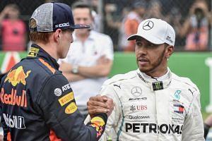 Hamilton (right) shakes hand with Max Verstappen after the qualifying session.