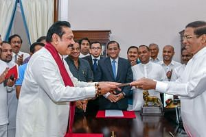 Sri Lankan President Maithripala Sirisena (right) handing over documents to former president Mahinda Rajapaksa during the swearing-in ceremony for prime minister at the President's Secretariat at Colombo last Friday.