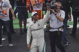 Mercedes' British driver Lewis Hamilton records the crowd as he celebrates his fifth drivers' title after the F1 Mexico Grand Prix on Oct 28, 2018.