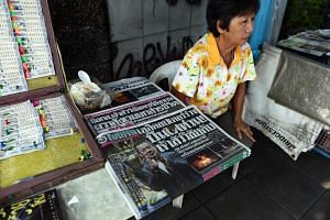 A vendor with newspapers carrying articles about Leicester City chairman Vichai Srivaddhanaprabha's helicopter crash at her stand in Bangkok, on Oct 29, 2018.