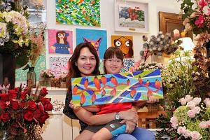 Florist Tara Chia and her daughter Ling Chu, who has Down syndrome, in a section of her shop with paintings by members of the DSA for sale.