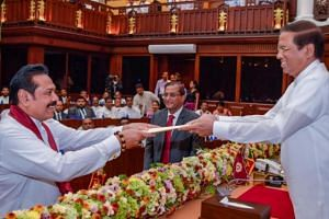 Sri Lanka's newly appointed Prime Minister Mahinda Rajapaksa (left) being sworn in as the Minister of Finance and Economic Affairs before President Maithripala Sirisena in Colombo, Sri Lanka, on Oct 29, 2018.