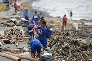 Workers removing debris washed ashore along the bay walk in Manila on Oct 30, 2018.