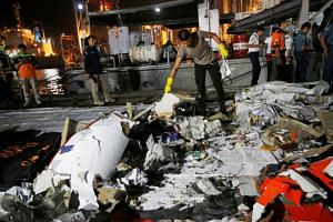 An Indonesian policeman holds wreckage recovered from Lion Air flight JT610 which crashed into the sea, at Tanjung Priok port in Jakarta, on Oct 29, 2018.