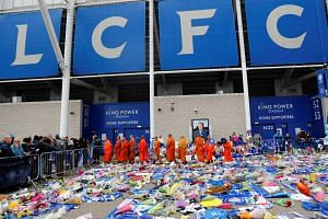 Bhuddhist monks leave after standing in tribute for the accident victims at the King Power Stadium, in Leicester, Oct 30, 2018.