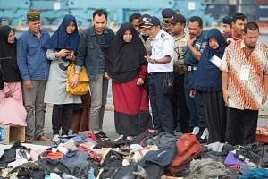 Relatives of passengers who were on board the ill-fated Lion Air flight JT610 identifying personal items at a port in Jakarta on Oct 31, 2018.