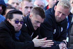 Aiyawatt Srivaddhanaprabha looking at flowers and messages of condolence with players Jamie Vardy and Kasper Schmeichel.